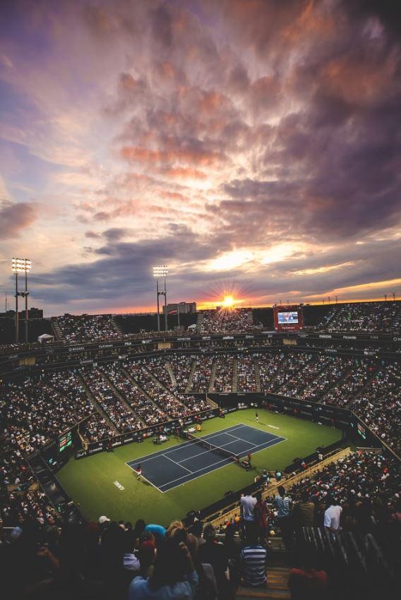 Kort tenisowy z pełnymi trybunami dookoła.