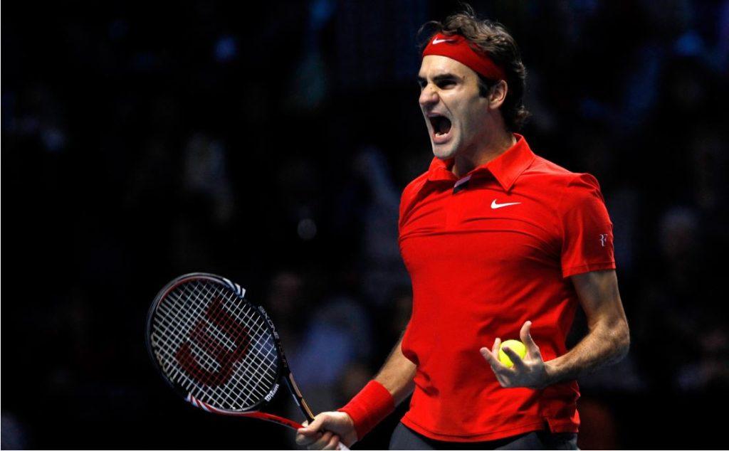 Roger Federer trzymający rakietę i piłkę w walecznej postawie