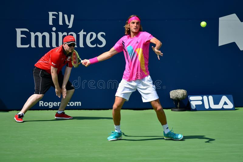 Tsitsipas Stefanos odbija piłkę z forhandu na turnieju ATP. Ubrany jest w różową koszulkę i białe spodenki