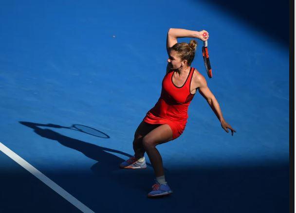 Profesjonalna tenisitka Simona Halep ubrana w czerwoną sukienkę tenisową wykańcza uderzenie tenisowe.