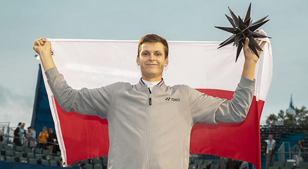 Hubert Hurkacz trzymający w ręku flagę Polski i figurkę gwiazdy