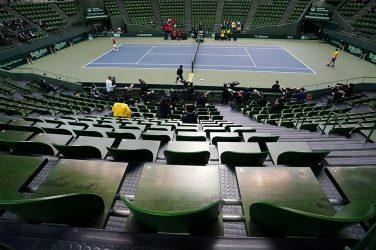 Kort tenisowy z pustymi trybunami w hali