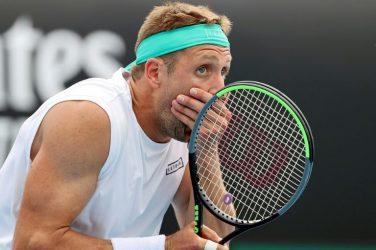 Tenisista Sandgren podczas zaskoczony zasłania buzię podczas meczu tenisowego z rakietą w ręku