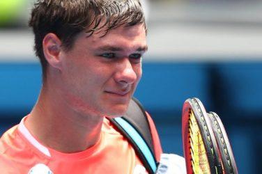 Kamil Majchrzak zmęczony po meczu tenisowym z rakietami w ręku